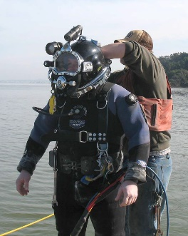 An outfall inspection diver suiting up.