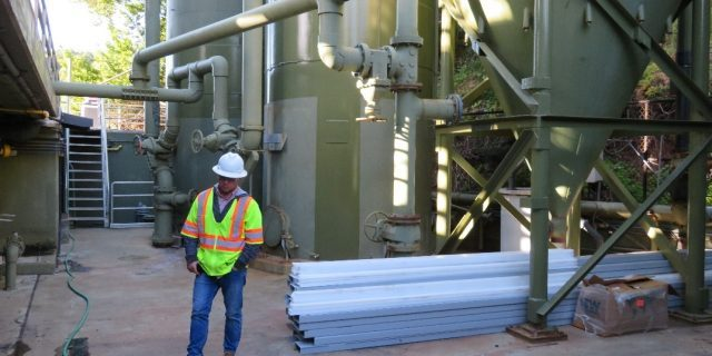 Worker standing next to sand filter.